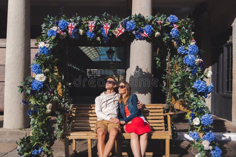 J?ntese en el amor asentado en un banco de balanceo en el jard?n covent Londres foto de archivo