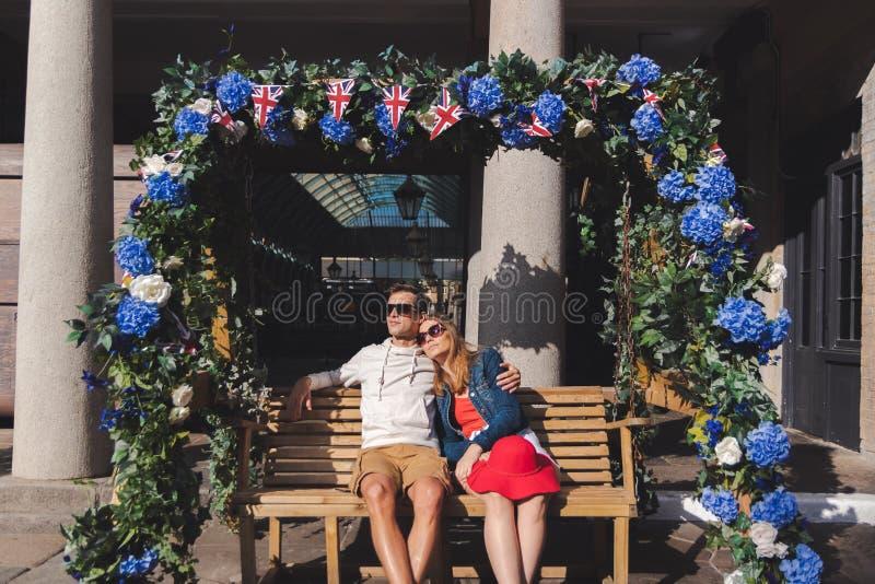 J?ntese en el amor asentado en un banco de balanceo en el jard?n covent Londres fotografía de archivo
