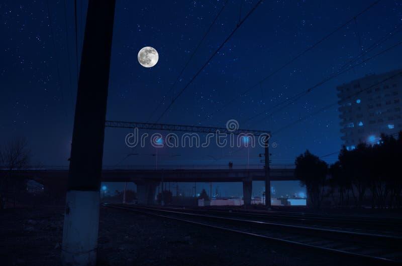 J?rnv?g i natt under fullm?nen H?rligt nattlandskap med bron ?ver j?rnv?gen royaltyfri bild