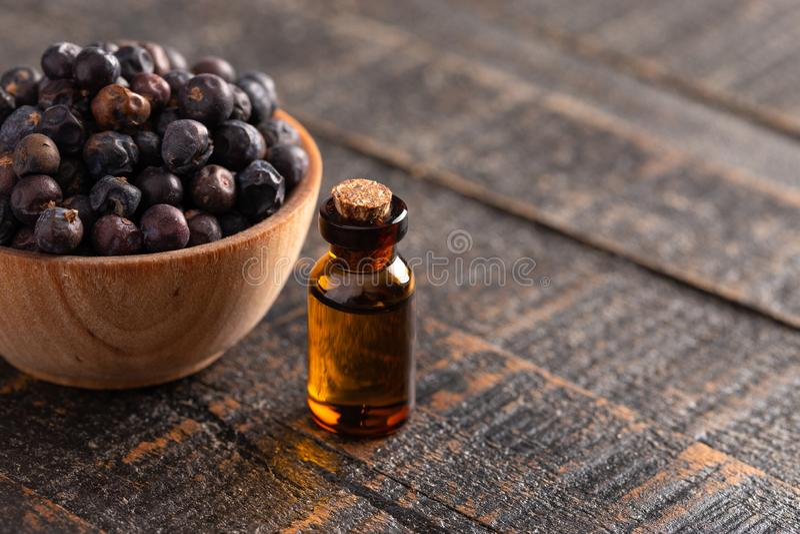 Jałowcowej jagody Istotny olej na Zakłopotanym Drewnianym stole fotografia royalty free
