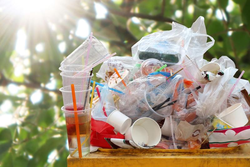 Jałowy plastikowy rozsypisko przy koszem, Niszczy pełnego kosza odpady śmieci, plastikowych worków jałowi dżonka na natury światł fotografia royalty free