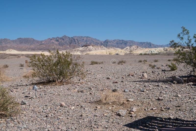 Jałowy pustynny piaskowaty krajobraz Śmiertelny Dolinny park narodowy w Kalifornia z bylicą i góry w tle, fotografia royalty free