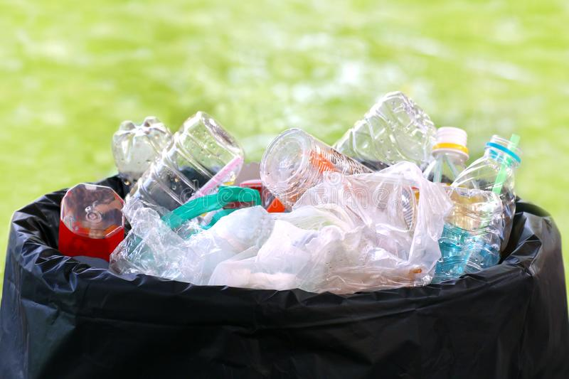 Jałowy rozsypisko klingeryt na koszu, Jałowego Śmieciarskiego grata plastikowy kosz na śmieci pełny, plastikowych worków jałowi d zdjęcia royalty free
