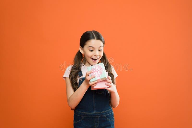 Ja łapał ona niespodzianką Śliczny mały dziecka otwarcia prezenta pudełko z niespodzianki twarzą na pomarańczowym tle Uroczy ma?y zdjęcie royalty free