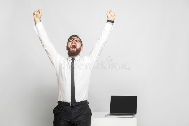 Ja! De gelukkige gillende gebaarde jonge zakenman in wit overhemd en de avondkleding bevinden zich dichtbij zijn werkende plaats  stock afbeelding