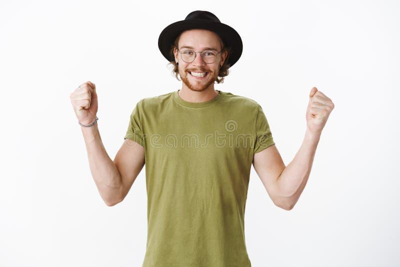 Ja deden wij het Portret van emotioneel gelukkig en verrukt knap jong hipster gebaard mannetje in glazen en hoed het glimlachen stock foto's