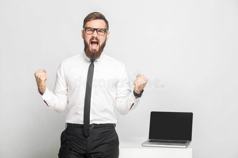 Ja! Het portret van knappe gelukkige gebaarde jonge zakenman in wit overhemd en de avondkleding bevinden zich in bureau zegeviere stock foto