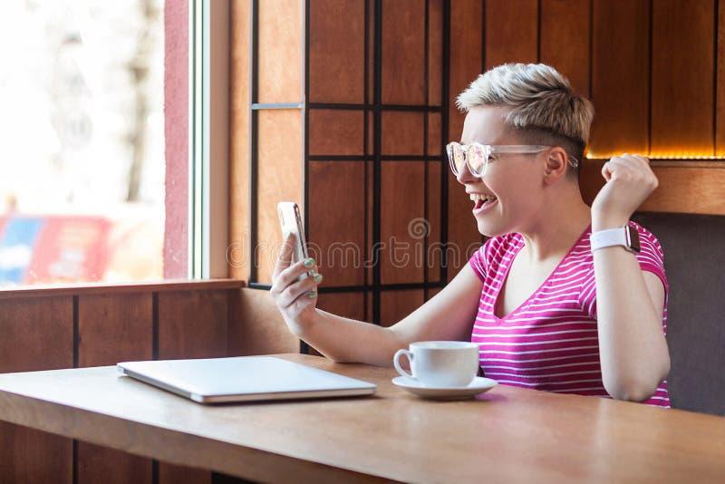 Ja! Het zijaanzichtportret van gelukkige die jongelui blogger met kort haar in roze t-shirt worden verrast zit in koffie, houdend royalty-vrije stock fotografie
