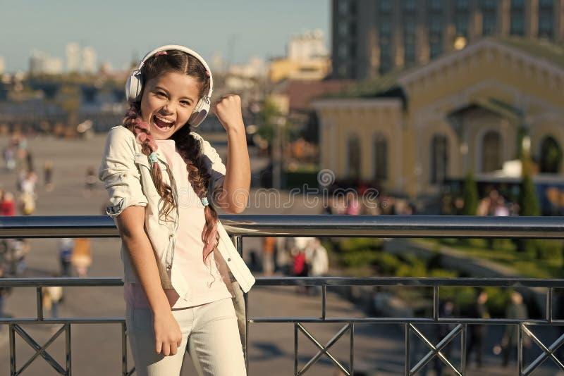 Ja, ich habe es getan Happy kleines Mädchen in Ohrhörern zeigt Gewinner Geste Kleines Kind mit Stereo-Soundtechnologie Neu stockfoto