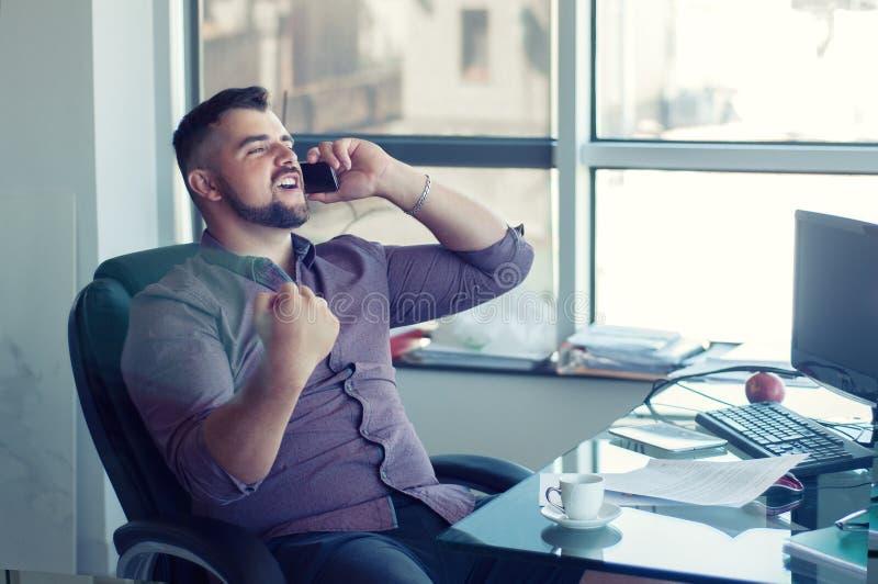 Ja! Ik deed het! Portret van gelukkige succesvolle zakenman in offic stock afbeelding