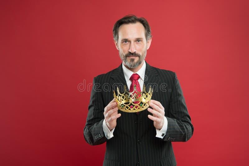 Ja jest jego dumnym przechwałki źródłem duma Dumny biznesmena mienia korony klejnot z dumą na czerwonym tle dojrza?y m??czyzna zdjęcie stock