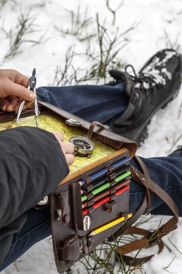 Ja jest zimny w zimie, ja snowing Dziewczyna z cyrklową mapą i drogomierz w ręce, brukujemy trasę tam tonuje obrazy stock