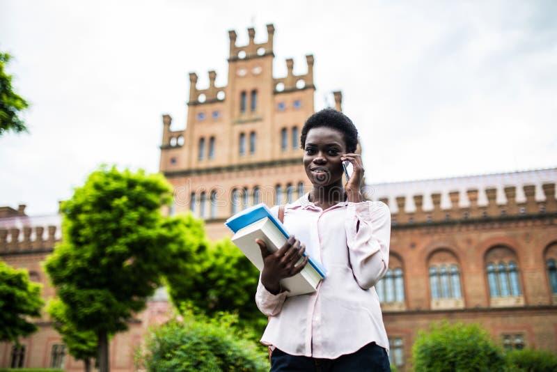 Ja passerar jag examen Ung nätt afrikansk amerikanhögskolestudent som gör en påringning utomhus- på universitetsområdet arkivbild