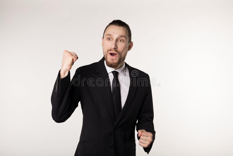 ja Vinnare Den eleganta unga mannen är stå och göra en gest för segern på vit bakgrund i svart dräkt och band arkivbild