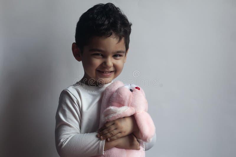 5 jaar aanbiddelijk weinig jong geitjejongen die met het konijntjesstuk speelgoed van het pluchekonijn spelen royalty-vrije stock foto