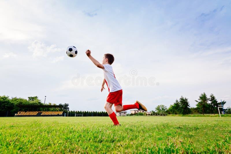 8 jaar de oude van het jongenskind speelvoetbal stock foto's