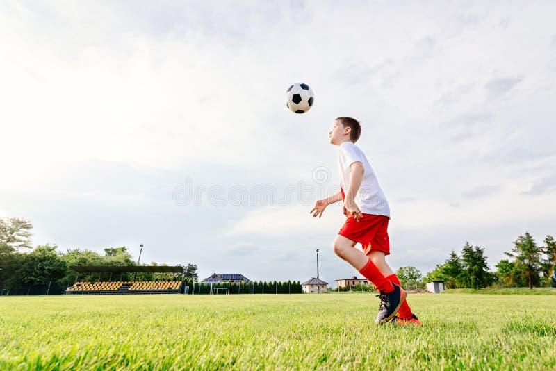 8 jaar de oude van het jongenskind speelvoetbal stock fotografie