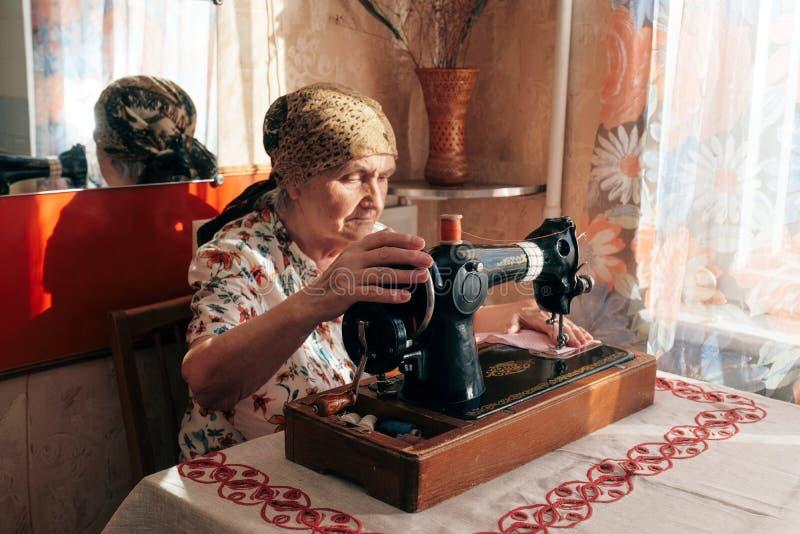 70 jaar het oude vrouw thuis naaien, hogere naaisterszitting bij bureau voor naaimachine, haar handen die roze stof duwen stock fotografie