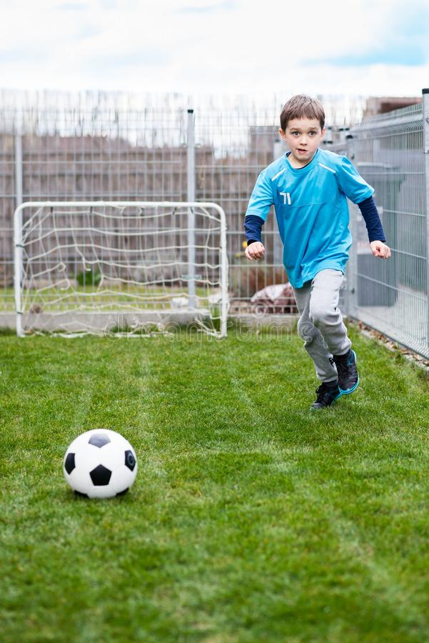 7 jaar jongen het schoppen bal in de tuin stock fotografie