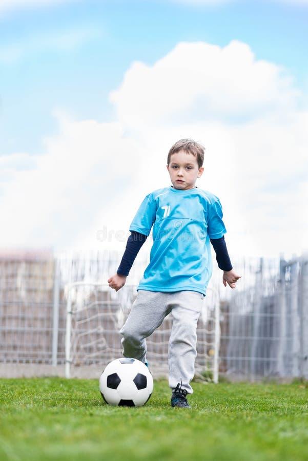 7 jaar jongen het schoppen bal in de tuin royalty-vrije stock afbeelding