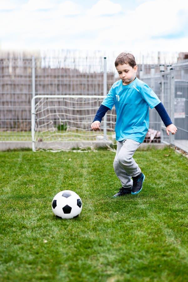 7 jaar jongen het schoppen bal in de tuin stock afbeeldingen