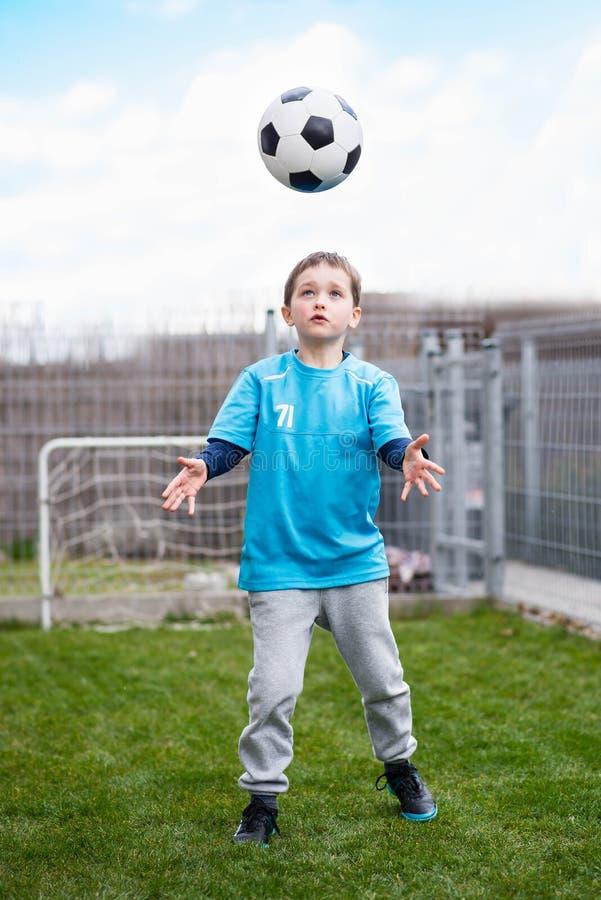 7 jaar jongen het schoppen bal in de tuin stock foto