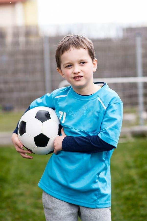 7 jaar jongens - voetballer met voetbalbal stock afbeeldingen