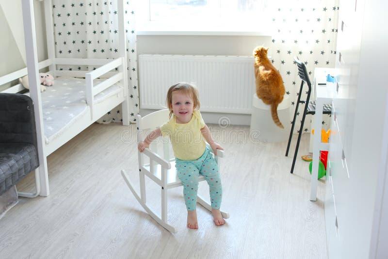 2 jaar meisje in haar ruimtezitting op een schommelstoel stock afbeeldingen