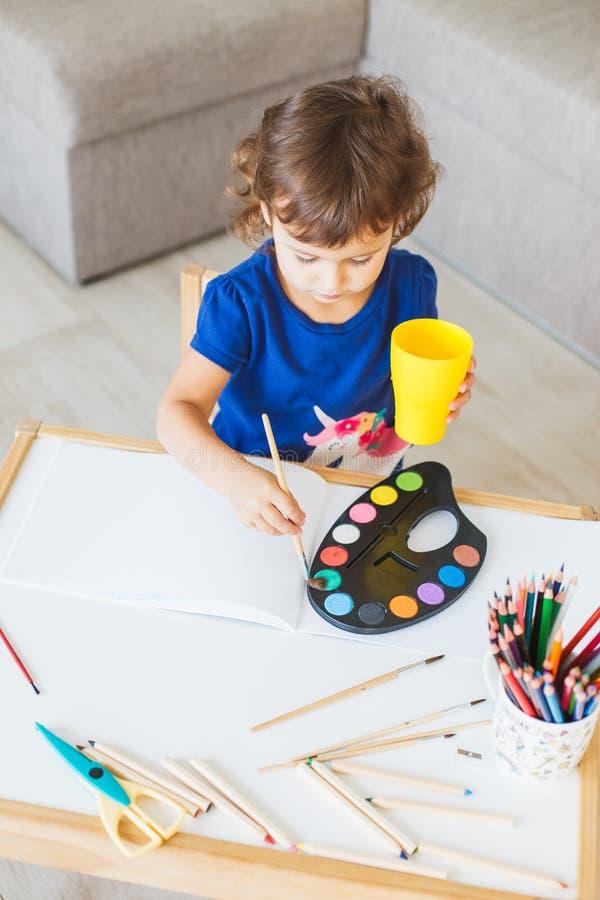 3 jaar meisje het schilderen bij de kleine lijst thuis royalty-vrije stock foto's