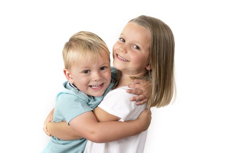 7 jaar oud aanbiddelijk blond gelukkig meisjes die met haar stellen weinig 3 jaar oude broer die vrolijk glimlachen geïsoleerd op stock foto's