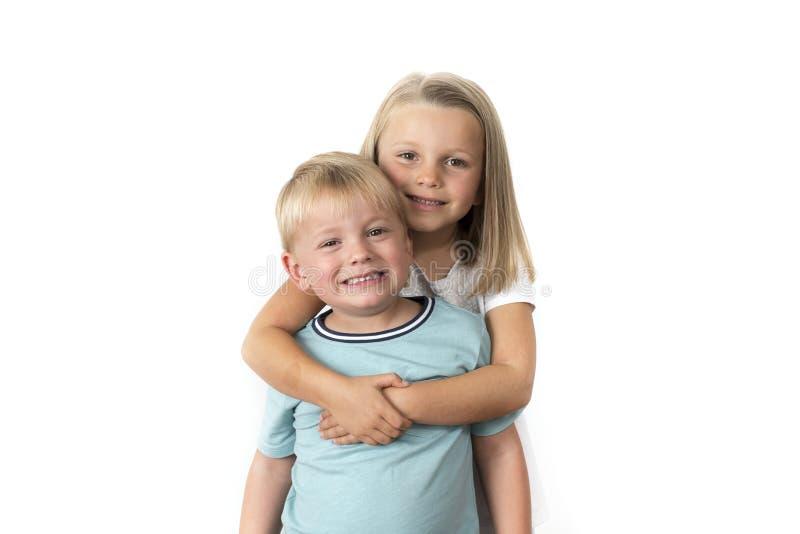7 jaar oud aanbiddelijk blond gelukkig meisjes die met haar stellen weinig 3 jaar oude broer die vrolijk glimlachen geïsoleerd op stock afbeeldingen
