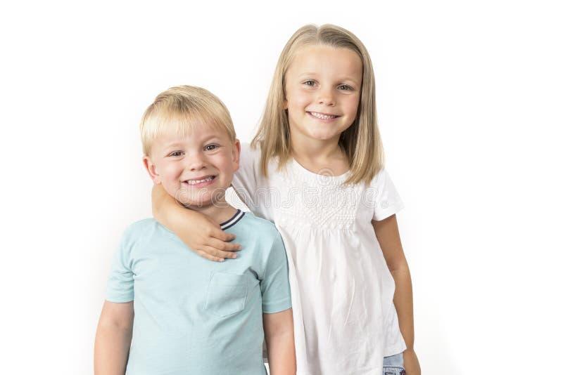 7 jaar oud aanbiddelijk blond gelukkig meisjes die met haar stellen weinig 3 jaar oude broer die vrolijk glimlachen geïsoleerd op royalty-vrije stock afbeeldingen