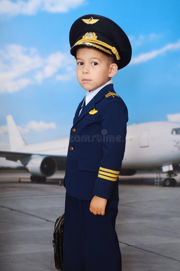 4 jaar oude jongen in een pilotenpak dat voor het vliegtuig in stand wordt gehouden royalty-vrije stock fotografie