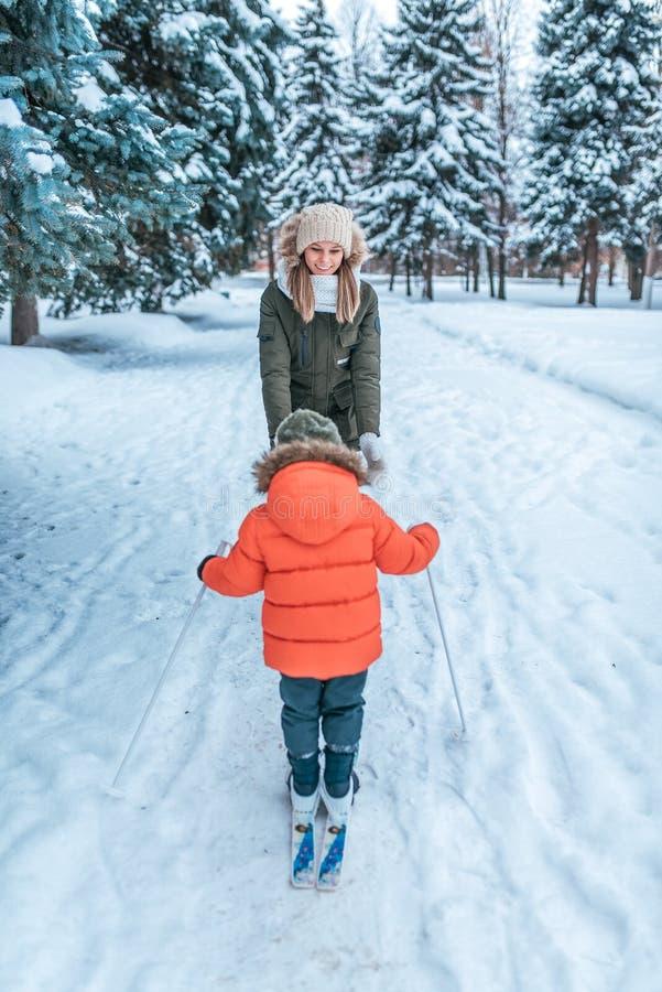 3-5 jaar oude jongensritten en gangen op stuk speelgoed die met jonge moeder ski?en De winter bosafwijkingen en houten afwijking  stock afbeelding