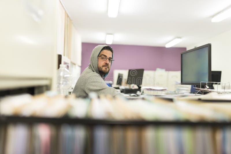 40 jaar oude mensen diecomputer en met sweatshirt werken kijken stock fotografie