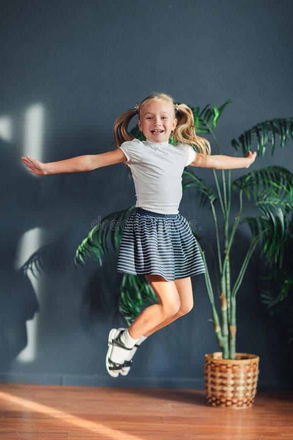 8 jaar oude Mooi verzamelde weinig blondemeisje zich met haar in staarten, witte t-shirt, witte sokken en grijze rok springend in stock foto