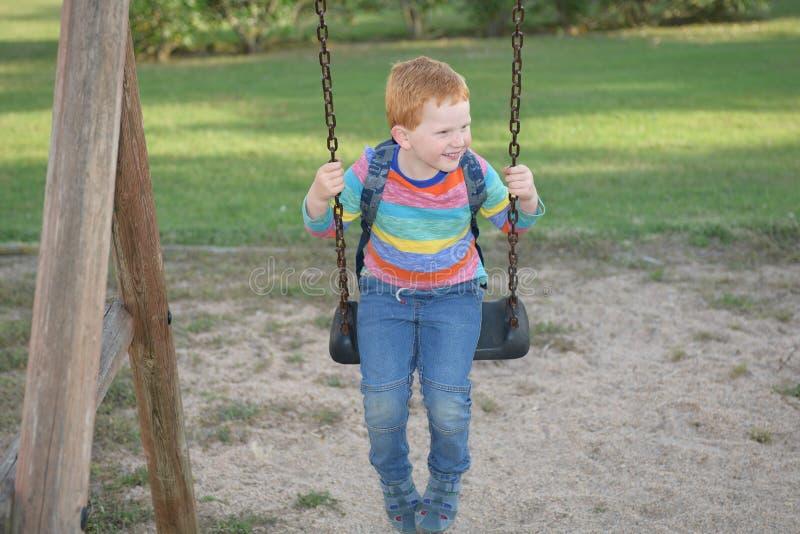 5 jaar oude redheaded gelukkige jongens met zijn en rugzak die slingert glimlacht stock afbeeldingen