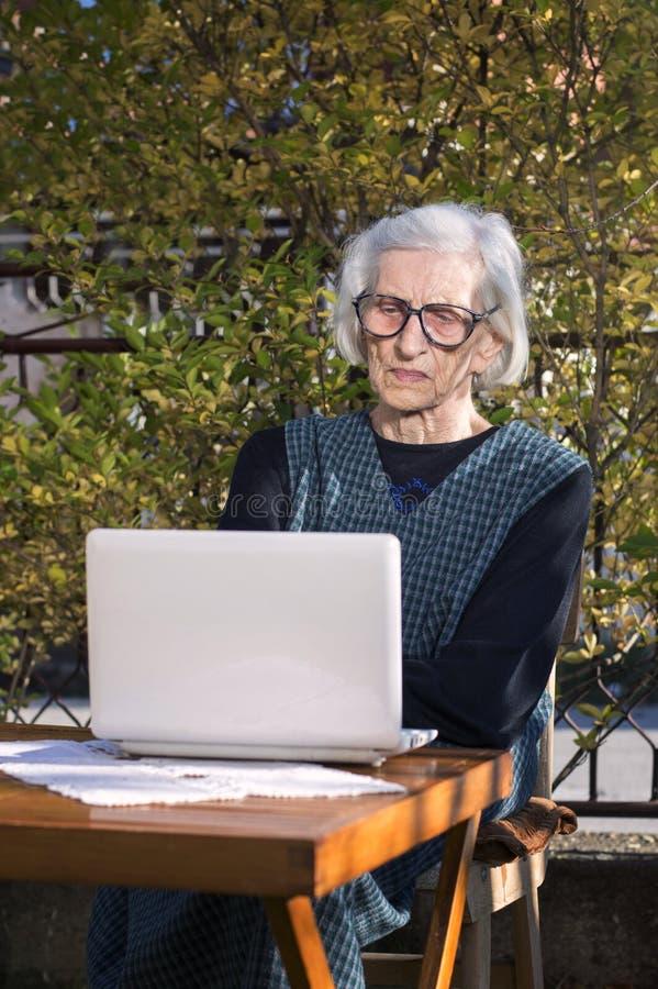 90 jaar oude vrouwen die een videovraag op een notitieboekje hebben royalty-vrije stock afbeelding