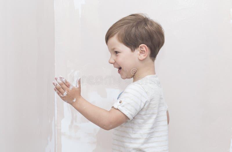 3 jaar weinig jongen die pret hebben terwijl hij thuis schildert stock foto's