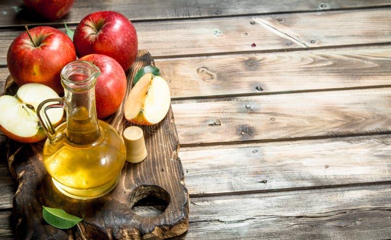 Jabłczanego cydru ocet z świeżymi czerwonymi jabłkami na tnącej desce zdjęcie royalty free