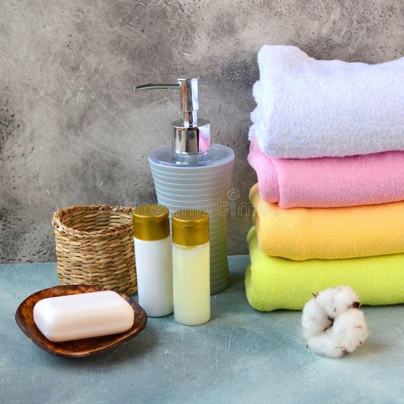 Jabón, champú, gel de la ducha, loción y toallas del algodón en la tabla contraria de piedra en un cuarto de baño fotos de archivo libres de regalías