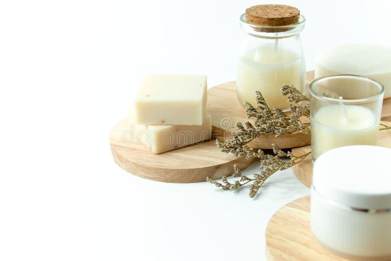 Jabón de la vela y del balneario con caspia de la flor y crema de la maqueta del cosmético con la placa de madera foto de archivo libre de regalías