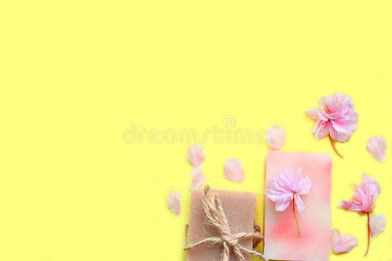 Jabón hecho a mano en un fondo amarillo, pétalos de la flor Espacio para un texto imágenes de archivo libres de regalías