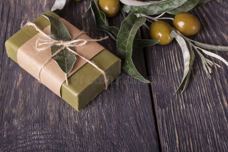 Jabón hecho a mano verde oliva con una rama fresca en de madera fotos de archivo libres de regalías