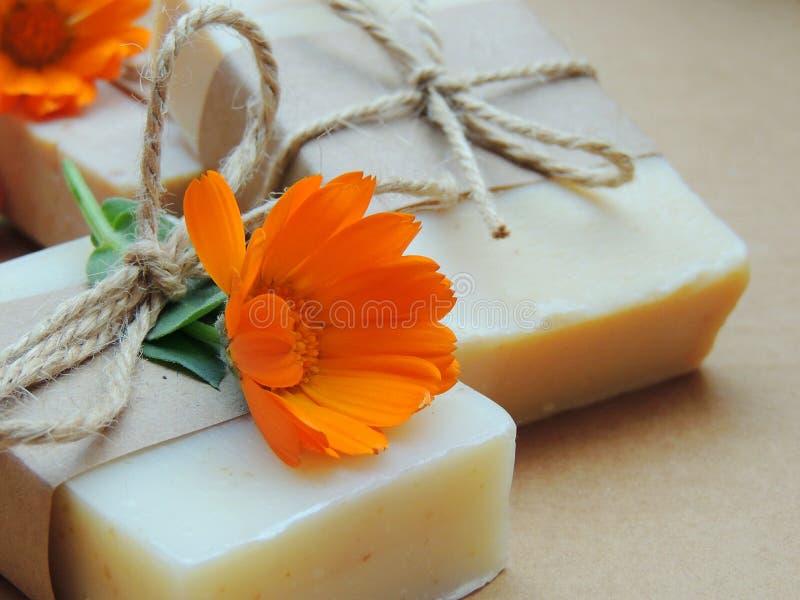 Jabón natural hecho a mano del calendula del baño del balneario del baño en fondo marrón Fabricación de jabón Jabón en manos imagen de archivo