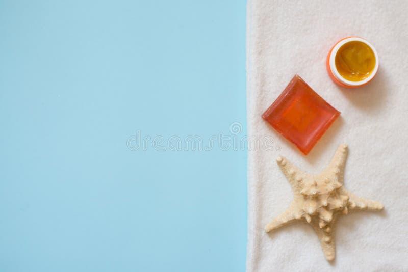 Jabón y estrella de mar anaranjados en la toalla blanca en fondo azul con el espacio de la copia Concepto del ba?o del balneario fotografía de archivo libre de regalías