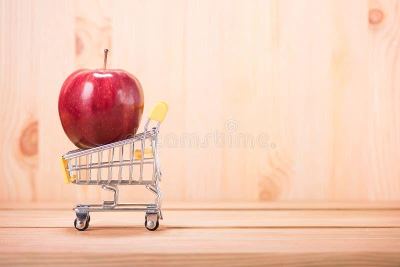 Jabłczana czerwień na wózku na zakupy z drewnianym podłogowym tłem obraz royalty free