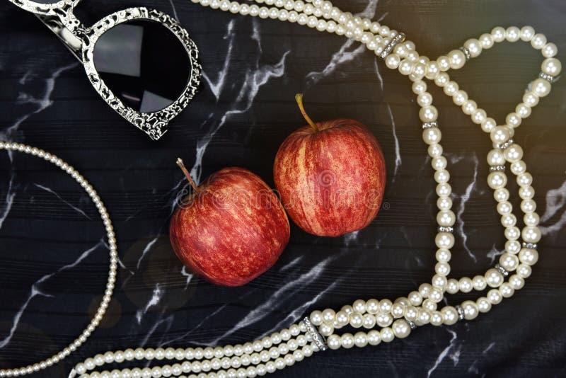 Jabłczana owocowa witamina jako naturalni kosmetyki, kobiet akcesoria, okulary przeciwsłoneczni, perełkowa kolia zdjęcia stock