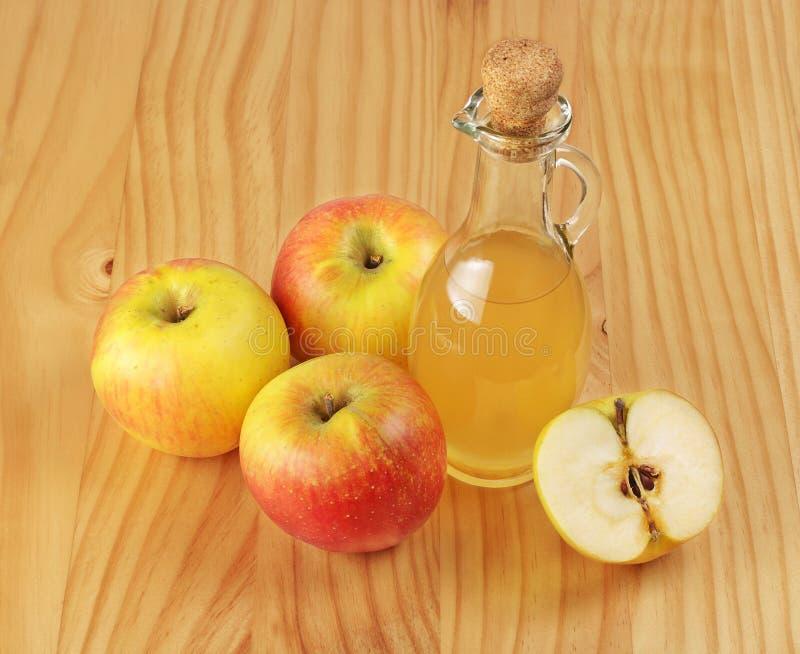 Jabłczanego cydru ocet i świeży jabłko na drewnianym tle fotografia royalty free