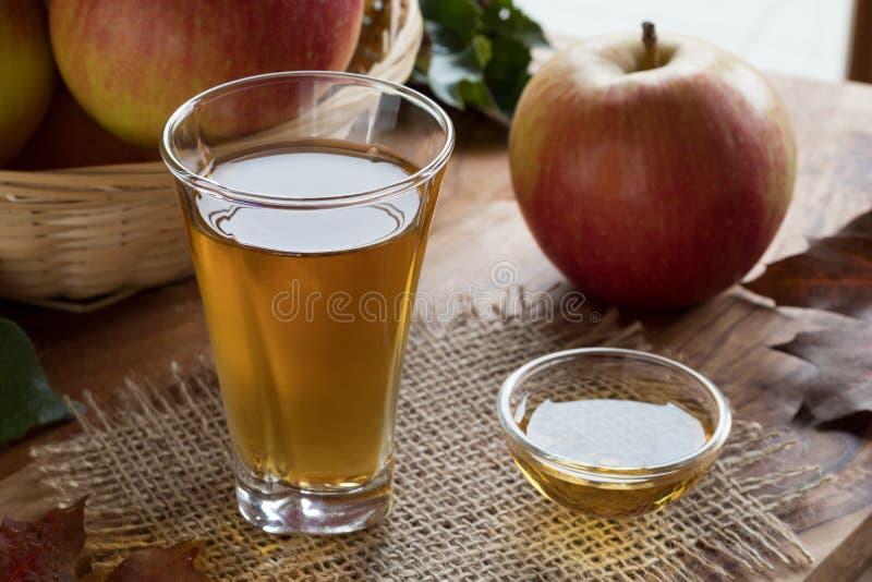 Jabłczanego cydru ocet w szkle z jabłkami w tle, zdjęcia royalty free